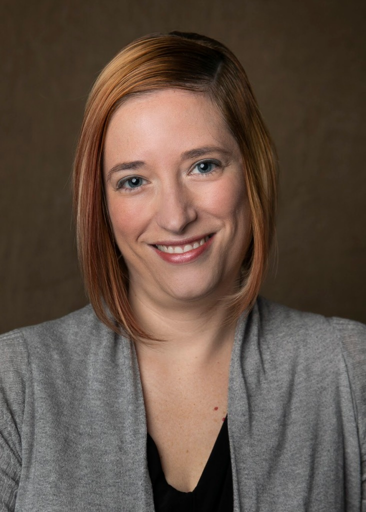 Professional headshot of Stacy smiling. She has straight reddish/blonde shoulder length hair  and she is wearing a light gray sweater over a black top.