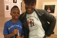 "The featured image is a photo of Wani and his mom Gracie. Wani is wearing a royal blue tee shirt that says ""Braille Code Inc."" on it in white letters. Gracie is wearing a white tee that has the 3 blind mice on it and above them is the title of the book. She is wearing a black leather jacket over her tee."