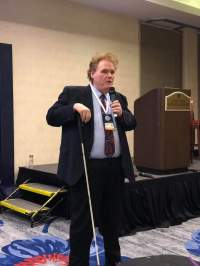 This is a photo of Max at a speaking engagement. He looks very professional in a suit and tie, holding the microphone his left hand and his white cane in his right. He is standing to the right of a podium at the front of the room.