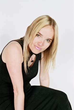 She is sitting, leaning forward, looking directly at the camera. Her straight blond hair parted in the middle frames her face. Wearing minimal makeup she is stunning with pink frosted lip color and is wearing a sleeveless black dress with a keyhole neckline.