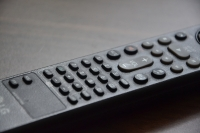 A black & white close up of a tv remote control.