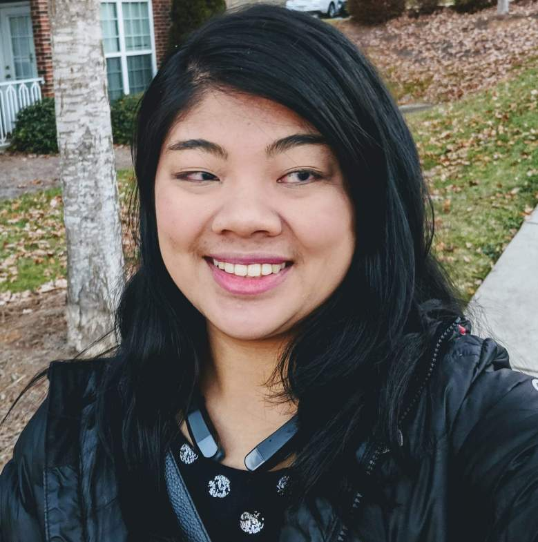 utdoor selfie of Carrie Morales smiling. Carrie's long black hair frames her pretty face. She is wearing a black leather jacket and a black top embellished with silver accents on the neckline.