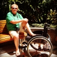 George is sitting on a park bench. His left leg is in the seat of his wheelchair, and his right leg is on the chair's footrest. He has reddish-blond hair, sunglasses, a green shirt, white shorts, and a camera around his neck.