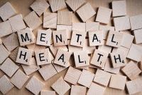 The image is Scrabble game pieces that spell out 'Mental Health.'