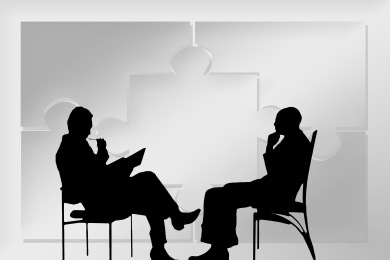 A black silhouette of a seated patient and therapist talking.
