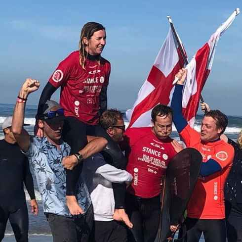 Melissa is on the shoulders of a couple of people in a crowd after a surfing win. Several people are holding English flags and are waving their arms.