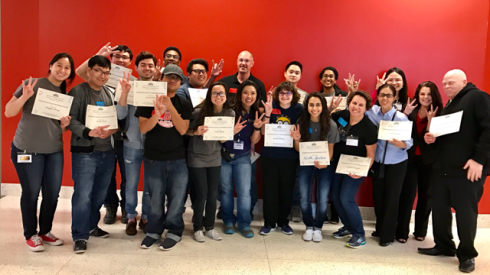HAVIN Insight Expo 2017 - group photo with volunteers. Chelsea Nguyen (Volunteer Coordinator) and Volunteer - Jeremy Bostic in the center all standing in a group smiling and making fun hand gestures in front of a red background and holding their Volunteer Appreciation Certificates.