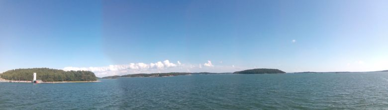 Panoramic view from the ferry. Blue skies with puffy white clouds in the distance. Tree-lined hills can also be seen afar.