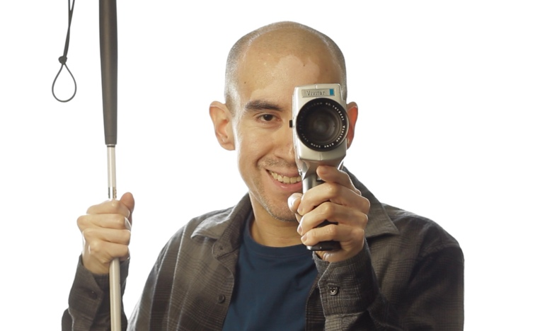 Juan Alcazar's photo shows him smiling while posing with his white cane and an 8mm camera.