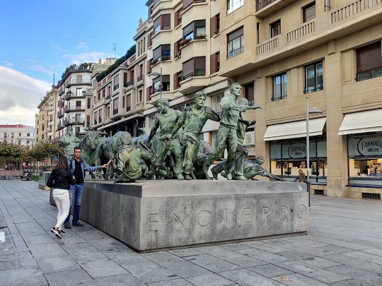 """The Monumento al Encierro (Bull Run Monument) is a full-scale bronze sculpture that depicts eleven spirited bulls charging through the streets, snorting on the heels of the runners (called mozos) as they sprint toward the Plaza de Toros with all their might. A few of the runners have stumbled and fallen to the ground, and this hyper-realistic monument depicts the anguish and fear etched on their faces."""