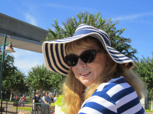 Photo has my wife Sandy wearing a soft blue and white striped hat with a large, floppy brim. She has on a matching top, dark sunglasses, and has long light-colored hair.