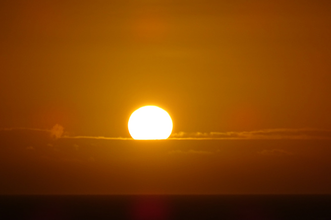 A hot, hazy sunset. The white sun is setting below a cloud bank is an orange sky.