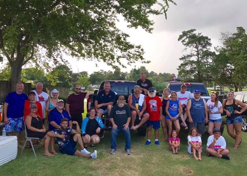 Chelsea and Jeremy with the group of TAA volunteers standing and sitting outside in the grass with several people sitting on two pickup truck beds.