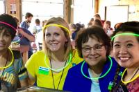 Header - Steph and Chelsea with Level Up Lead Coordinators: Hannah Christenson and Bonnie Cochran (center) at the taco bar sporting our glow in the dark accessories.