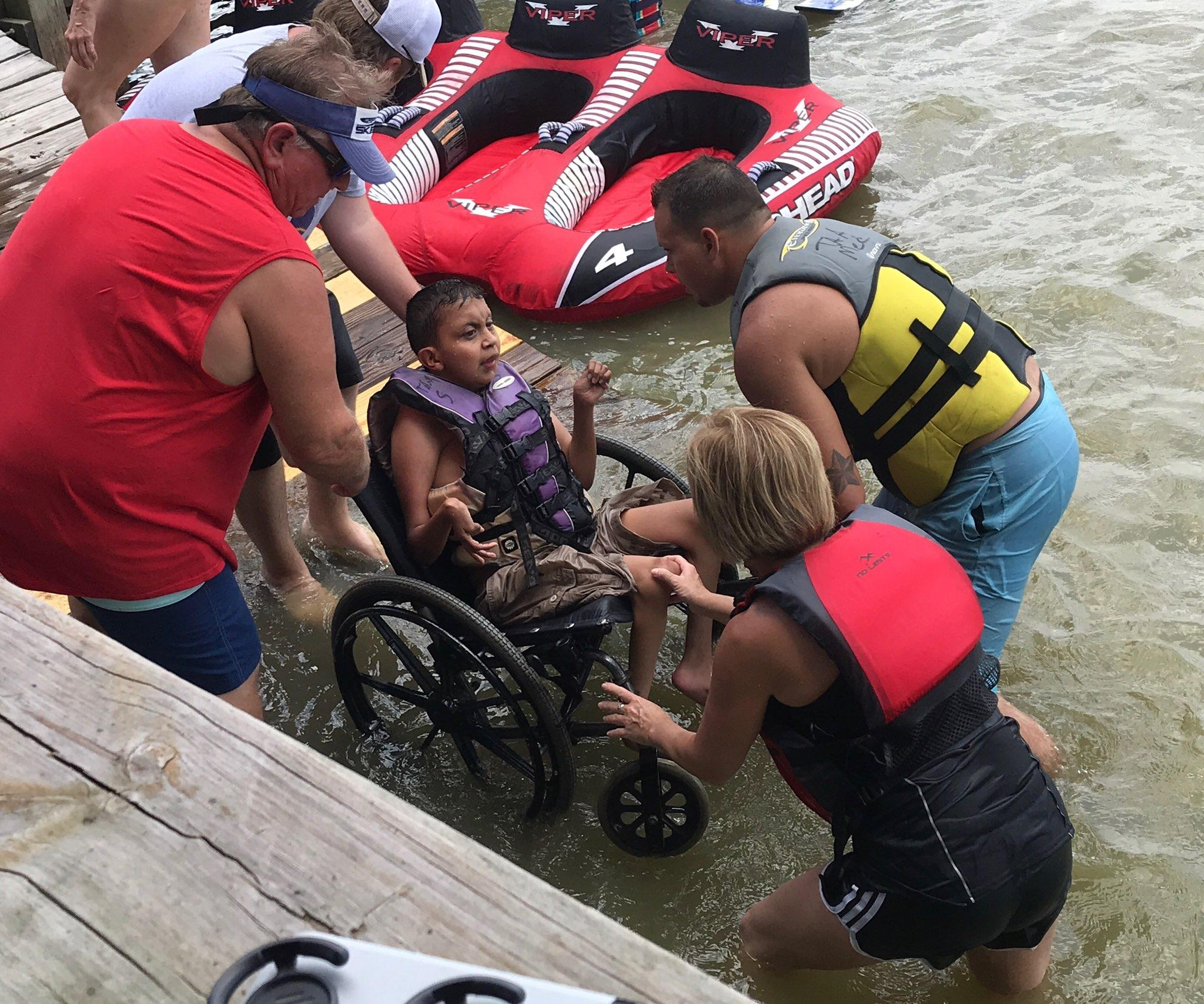 A little boy in a wheelchair is being helped into the water on a ramp by three TAA volunteers.