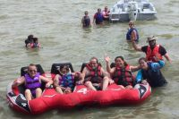 In this photo from left to right, a volunteer, JoAnn, Ted and I are sitting inside a big 4 person float tethered to the white boat behind us and we've got big smiles on our faces while waving goodbye before we go off for our wet ride over Lake Houston. To my left, smiling and waving too is Lindi Mouton, who is a PTA (Physical Therapist Assistant) who is one of several other volunteers that helped us get into our float safely.