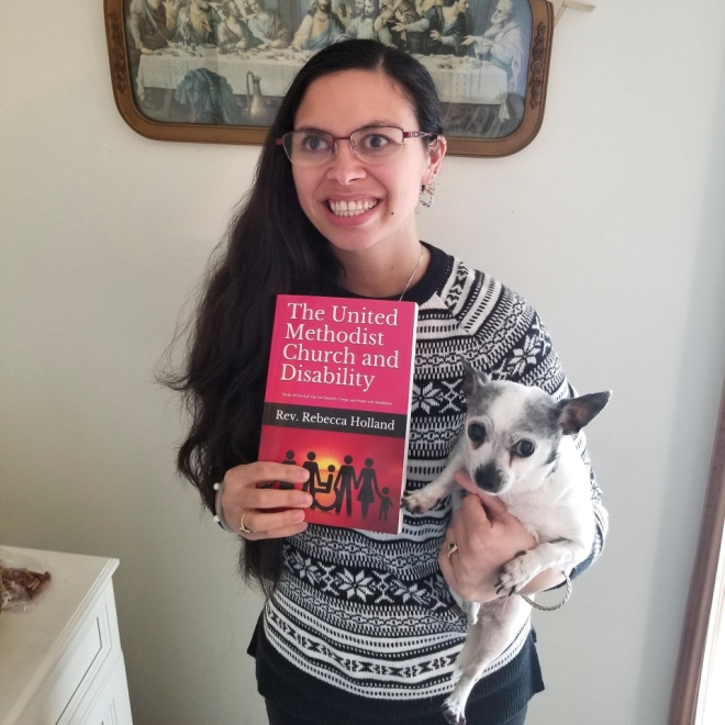 Rebecca holds a copy of her new book and her writing buddy. Her book has a red cover and her writing buddy is an elderly white chihuahua named Tinkerbell.
