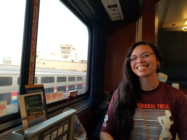 Leaving Chicago by overnight train, Rebecca sits in a sleeper car and smiles
