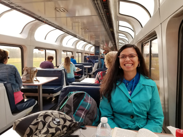 Rebecca smiles while seated in the observation car on Amtrak.