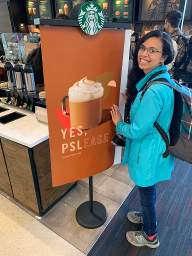 Rebecca stands by a large sign advertising the Starbucks Pumpkin Spice Latte.