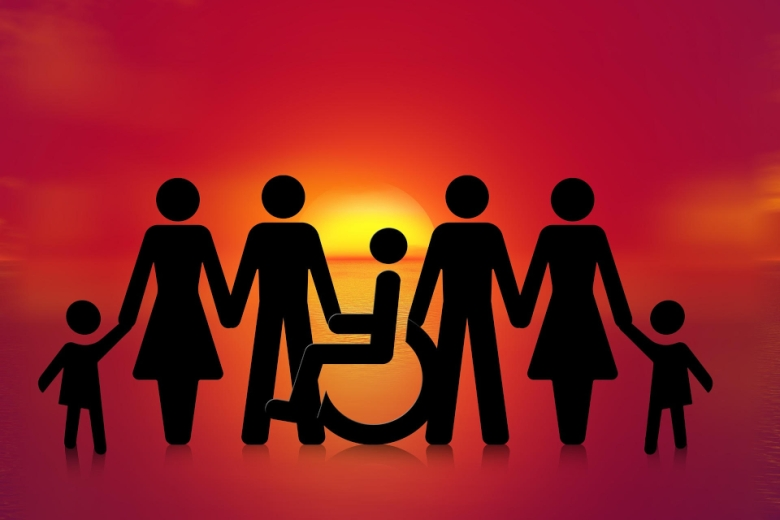 Silhouettes of people in pants, people in dresses, and children stand holding hands with the silhouette of a wheel seated in a wheelchair. The sun rises in the background.
